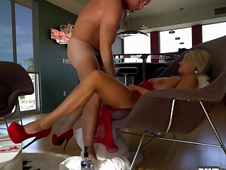 Mila in a red dress is engaged in sex on a chair with Carl